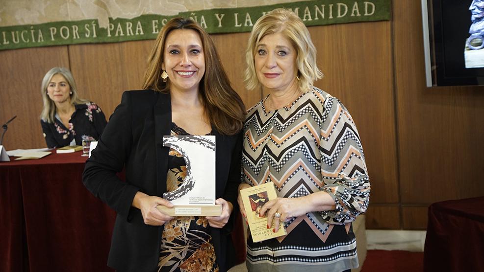 Mª del Carmen Candel recibe el premio a título póstumo de su madre, M! del Carmen Martín, de la mano de Blanca Fernández, presidenta del COOOA