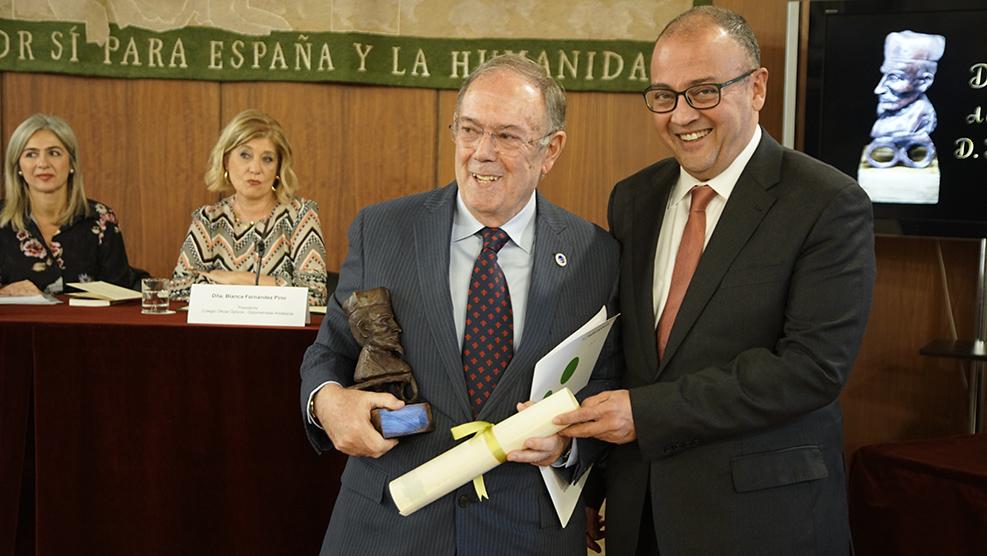 El óptico-optometrista Juan Fernández-Baca recoge su premio de la mano de Jorge Maguilla, tesorero del COOOA